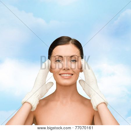 beauty, winter, people and health concept - smiling young woman in white mittens over blue sky background