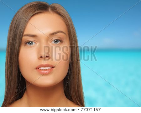 beauty, people, vacation and health concept - beautiful young woman with bare shoulders over blue sea and sky background