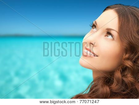 beauty, people and health concept - beautiful young woman looking up over blue sky and sea background