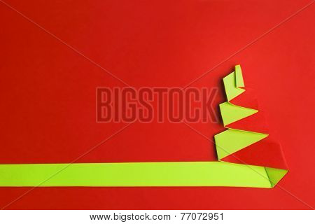 Red background with Conceptual paper christas tree and copy space