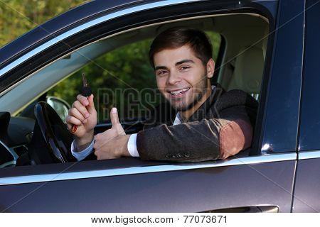 Man with car key in car