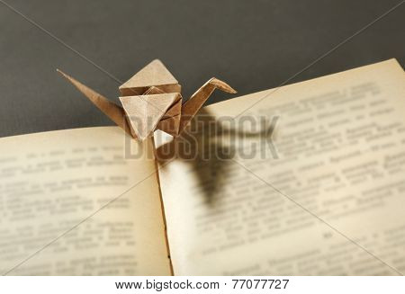 Origami cranes on old book on grey background