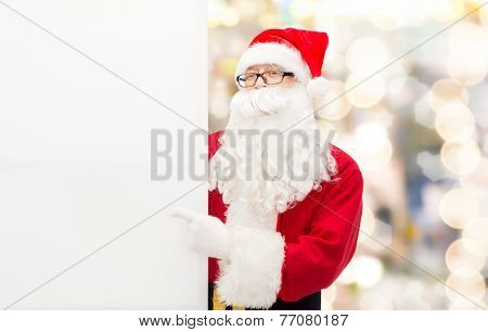 christmas, holidays, advertisement, gesture and people concept - man in costume of santa claus pointing finger to white blank billboard over lights background