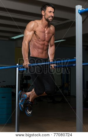 Bodybuilder Exercising On Parallel Bars