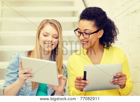 education and technology concept - smiling female students with tablet pc computer sitting on staircase