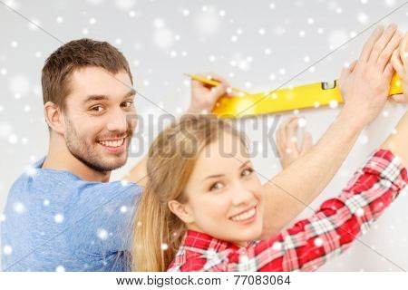 repair, building, people and new home concept - smiling couple measuring wall by spirit level