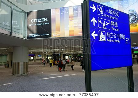 Passagers Arrive In The Arrival Hall Of Hong Kong Airport