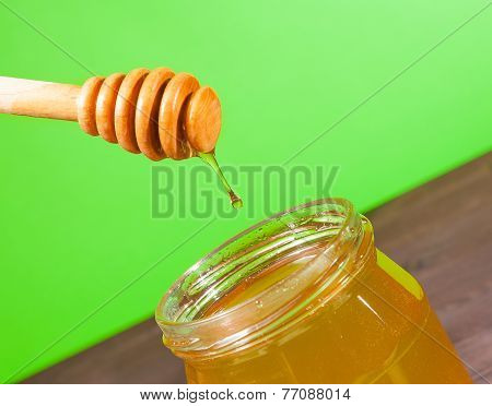 Honey Jar On Wood Table And Green Background With Wooden Honey Dipper On Top With Drop Honey