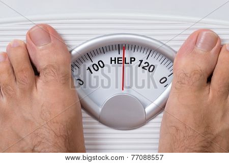 Man's Feet On Weight Scale Indicating Help