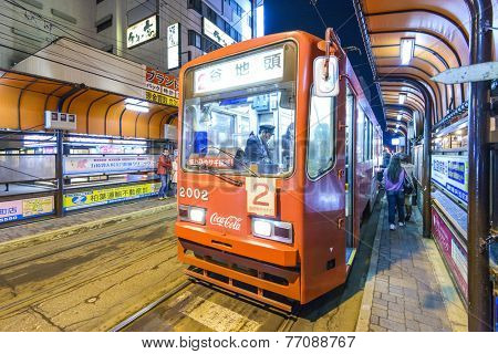 HAKODATE, JAPAN - OCTOBER 25, 2012: Passengers alights from the tram. The tram originates from 1897 and is a local landmark as well as an efficient means of transit.