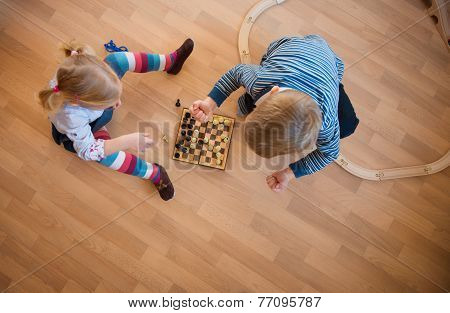 Brother And Sister Playing With Chess