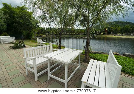 White Wooden Table And Benches At The Lakeside In Nice Park