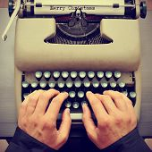 foto of typewriter  - a young man typewriting the text merry christmas in a paper sheet on an old typewriter - JPG