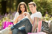 stock photo of nibbling  - A young couple resting on a park bench after shopping enjoying the autumn sun while nibbling popcorn - JPG