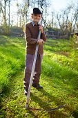 stock photo of scythe  - Senior farmer mowing the lawn with a scythe traditionally - JPG