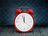stock photo of count down  - Alarm clock counting down to twelve against dark grimy room - JPG