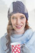 stock photo of glass-wool  - Pretty redhead in warm clothing holding mug seen through glass window - JPG