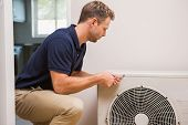 foto of handyman  - Focused handyman fixing air conditioning in a new house - JPG