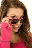 foto of peer  - Brunette woman peering over sun glasses smiling - JPG