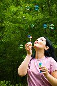 Woman Blowing Colorful Soap Bubbles