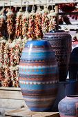 stock photo of pottery  - southwestern pottery in a shop in Santa Fe New Mexico with chilies hanging on the background - JPG
