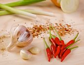 stock photo of scallion  - Red hot chilli peppers with a scallion and garlic on a wooden board - JPG
