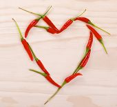 stock photo of red hot chilli peppers  - Red heart made of red hot chilli peppers on a wooden background - JPG
