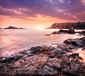 stock photo of karnataka  - Sea with rocks at violet sunset sky in Om beach Gokarna Karnataka India - JPG