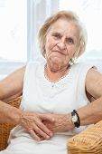 foto of 70-year-old  - Portrait of an elderly lady in her 70s sitting in a chair - JPG