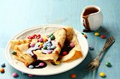 picture of crepes  - Homemade crepes with multicolored dragee and chocolate sauce on blue wooden background - JPG