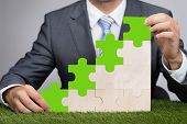 stock photo of jigsaw  - Midsection of businessman holding jigsaw graph on grass representing go green concept - JPG