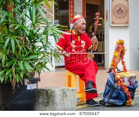 Senior street musician entertains people in Singapore's Chinatown