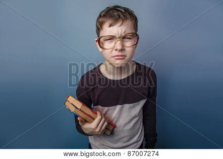 European-looking boy of ten years  in  glasses reading  a book o
