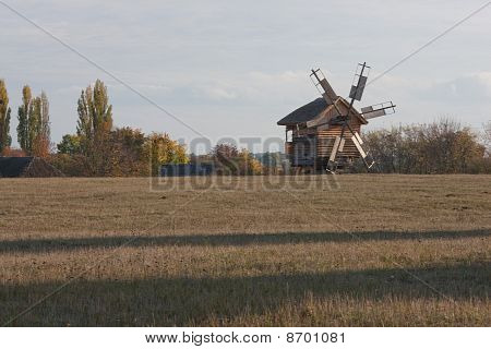 Autumnal Country Scenery. The Windmill  In The Field. Field With Dry Grass In The Foreground.