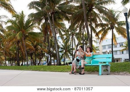 Female Asian Tourists Watch People Along Miami Beach Recreational Area