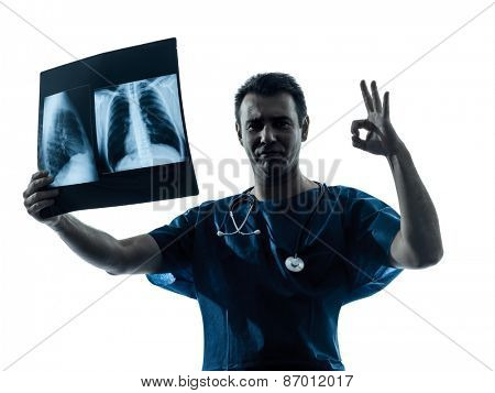 one  man doctor surgeon radiologist medical gesturing okay examining lung torso x-ray image silhouette isolated on white background