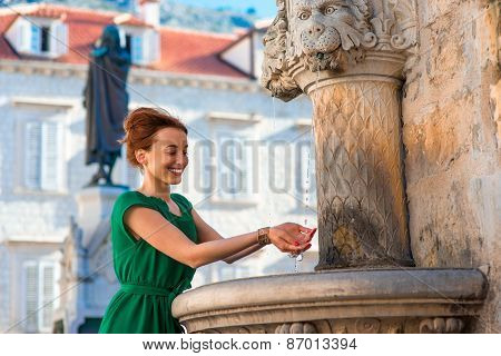 Woman drinking water from classical fountain in the city