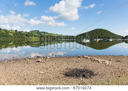 Barbecue ashes by beautiful lake on calm idyllic summer morning with cloud reflections