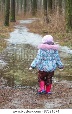 Two Years Old Girl Walking On Icy Puddle