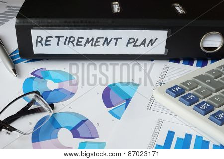 Graphs and file folder with label  retirement plan.