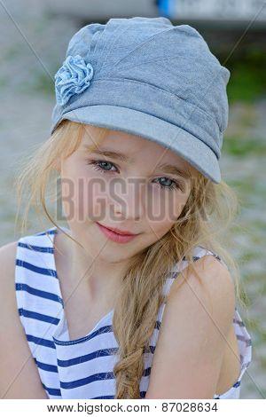 Portrait of small girl in denim cap outdoors