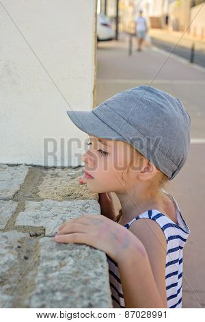 Little girl looking through a wall
