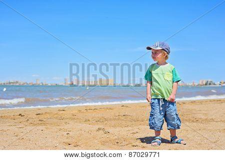 Small trendy boy standing sandy beach