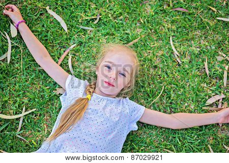 Caucasian small girl lay on grass