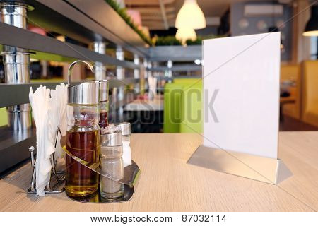 Bottles with olive oil, vinegar, salt and pepper, napkin on the table in restaurant