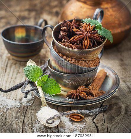 Cocoa powder, anise, sugar, vanilla pods in vintage silver cup