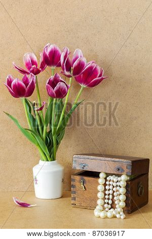 Bright Purple Flowers In A White Vase Tulips And Wooden Chest With Pearls