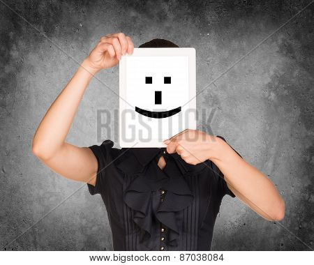 Girl in dress covered her face with tablet. On screen cheerful smiley