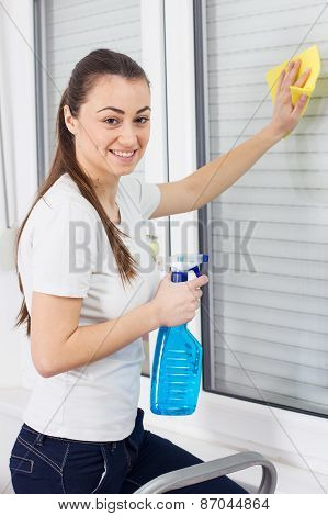 Young Woman Cleaning Windows Glass