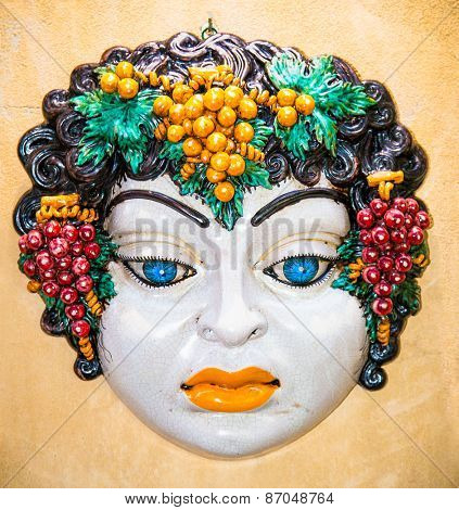 Woman face typical Sicilian glazed ceramic on wall in Taormina. Sicily, Italy.